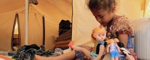 طفلة تلهو بدميتها في أحد مخيمات اللاجئين السوريين